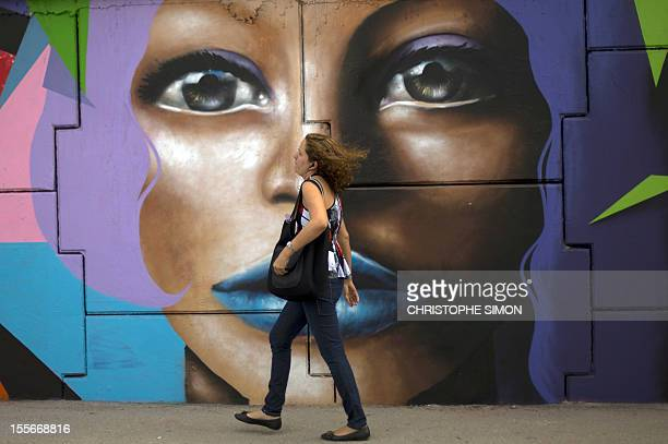 A woman walks by a graffiti on the wall of Maracana subway station in Rio de Janeiro on November 6 2012 Metro Rio asked grafitti artists to paint...