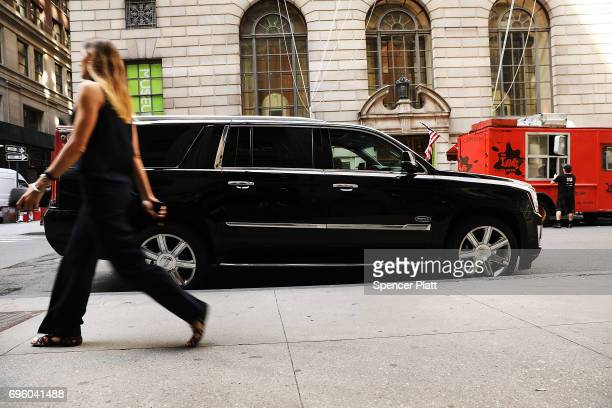 A woman walks by a hired SUV as it waits for a client in Manhattan a day after it was announced that Uber cofounder Travis Kalanick will take a leave...