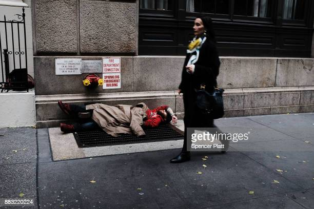 A woman walks by a homeless man along a Manhattan street on November 30 2017 in New York City Republicans are coming closer to getting the votes...