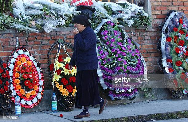 A woman walks by a memorial to the terror victims at School No 1 September 8 2004 in Beslan southern Russia Approximately 355 children and adults...