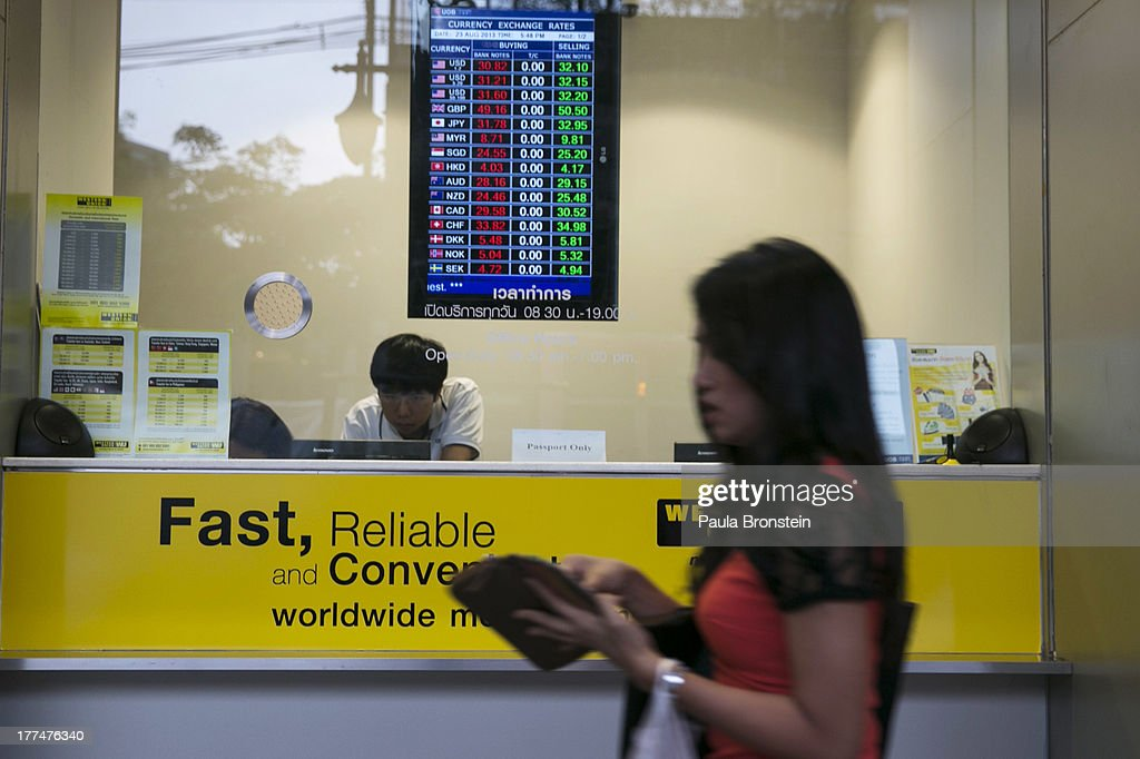 A woman walks by a money exchange bank kiosk on August 23, 2013 in downtown Bangkok, Thailand. The local currency dropped to its lowest level since August 2010. Against the US dollar the Thai baht fell to 32.09/32.13 dropping about 5% this year.