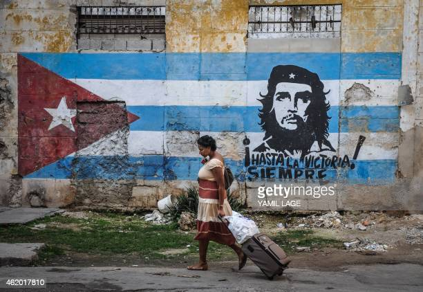 A woman walks by a mural with the Cuban flag and an image of revolutionary leader Ernesto Che Guevara in Havana on January 23 2015 Hours into...