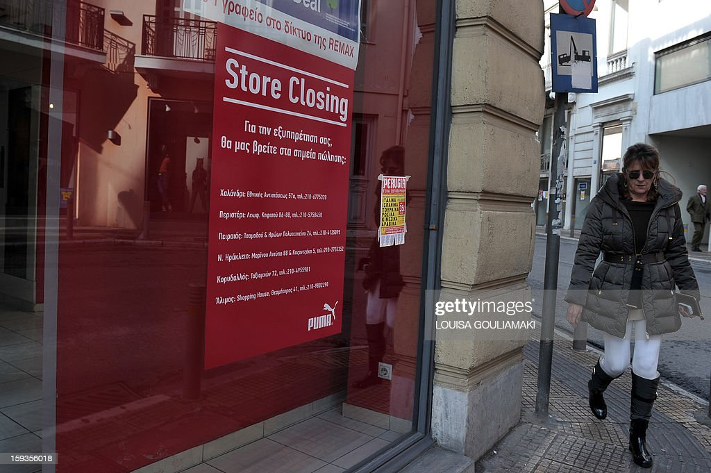 A woman walks by a newly closed store in central Athens on January 11, 2013. Greece's unemployment rate rose to a record high of 26.8 per cent in October, as the country headed into a sixth year of recession.
