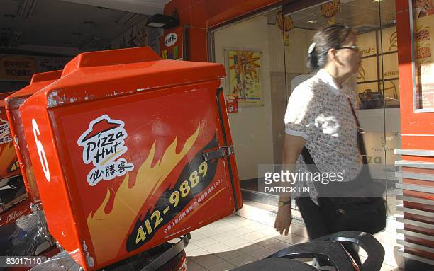 A woman walks by a Pizza Hut outlet in Taipei on September 26 2008 Taiwan's Pizza Hut had pulled grated cheese from its outlets after they were found...
