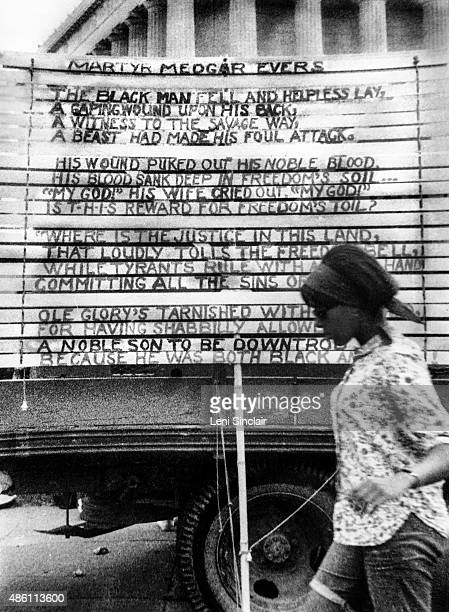 A woman walks by a Poem for Medgar Evers written on the side of a truck at the March on Washington August 28 in Washington DC