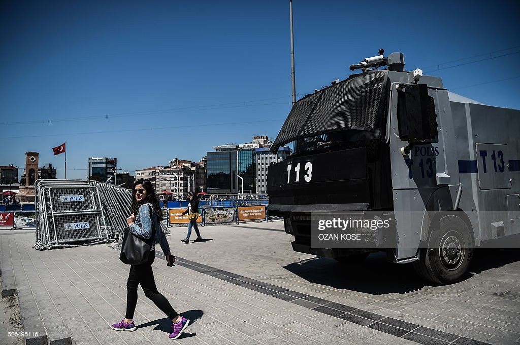 A woman walks by a police vehicle equipped with a water cannon at the Taksim square taken on April 30, 2016 in Istanbul, on the eve of May day. Istanbul braced for a major security lockdown for May Day on Sunday, with almost 25,000 police on duty and numerous roads closed for an occasion that regularly sees clashes between Turkish protesters and police. / AFP / OZAN