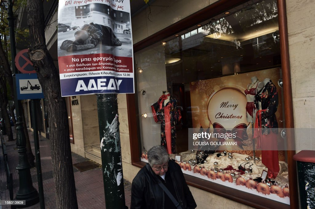 A woman walks by a private sector union's poster calling for the December 19 strike and featuring a homeless man with a slogan reading 'no to poverty of the people' on December 13, 2012 in Athens. Much-needed rescue funds for Athens 'will be flowing to Greece as early as next week,' the head of the Eurogroup Jean-Claude Juncker said on Thursday. AFP PHOTO / LOUISA GOULIAMAKI
