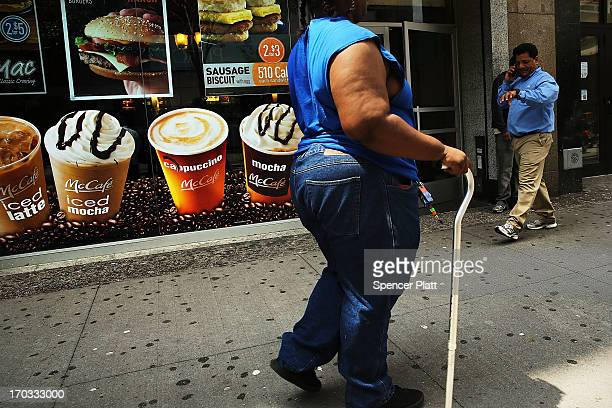 A woman walks by a sign advertising sugary drinks in a Brooklyn neighborhood with a high rate of obesity and diabetes on June 11 2013 in New York...