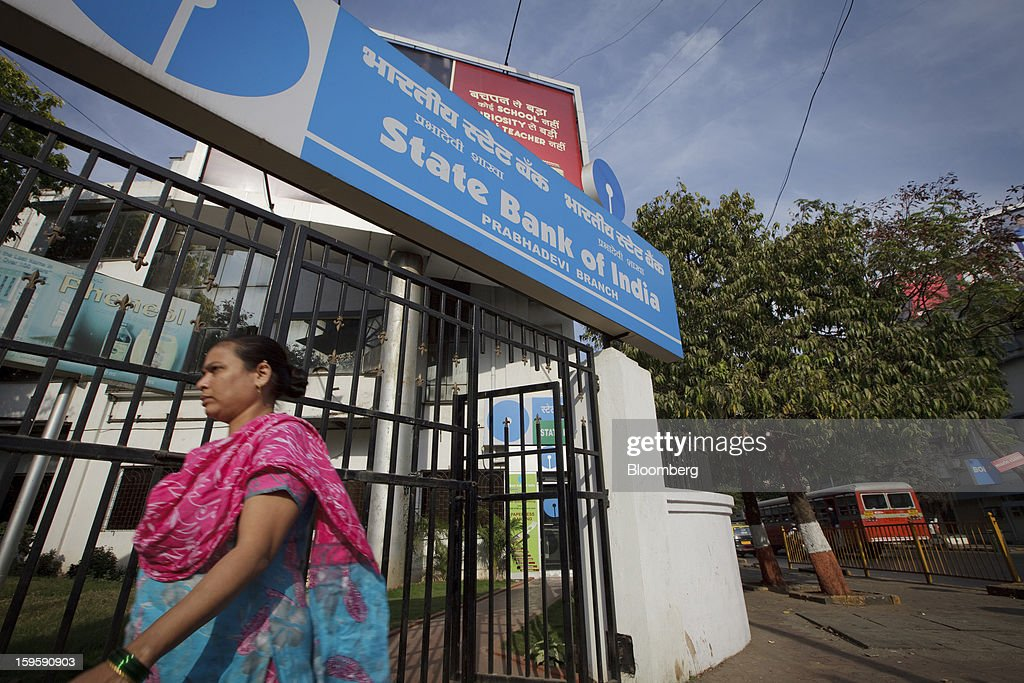 A woman walks by a State Bank of India bank branch in Mumbai, India, on Wednesday, Jan. 16, 2013. India's financial system has been made vulnerable by a deterioration in bank assets and a lack of capital as the economy slowed, according to the International Monetary Fund. Photographer: Kuni Takahashi/Bloomberg via Getty Images