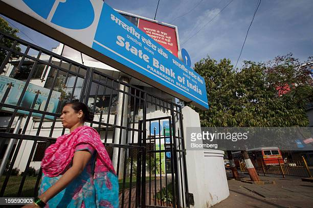 A woman walks by a State Bank of India bank branch in Mumbai India on Wednesday Jan 16 2013 India's financial system has been made vulnerable by a...