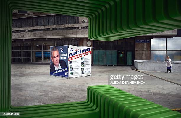 TOPSHOT A woman walks by an election campaign poster of candidate Nikolai Gonchar from the United Russia party on September 13 2016 in central Moscow...