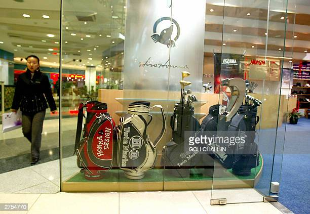 A woman walks by an empty golf shop at a shopping mall in Beijing 23 November 2003 In China golf has a reputation for being a sport only for the...