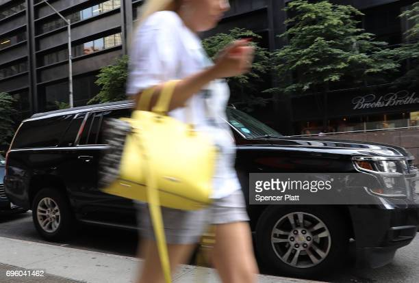 A woman walks by an Uber SUV as it waits for a client in Manhattan a day after it was announced that Uber cofounder Travis Kalanick will take a leave...