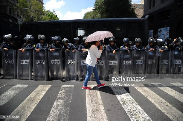 TOPSHOT A woman walks by as police officers stand guard during a farmers' march in Mexico City August 8 2017 as part of nationwide protests against...