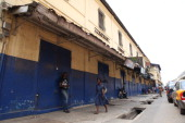 A woman walks by closed shops on June 24 2014 in Ghana's capital Accra as a major traders' union launched a fourday strike to protest against the...