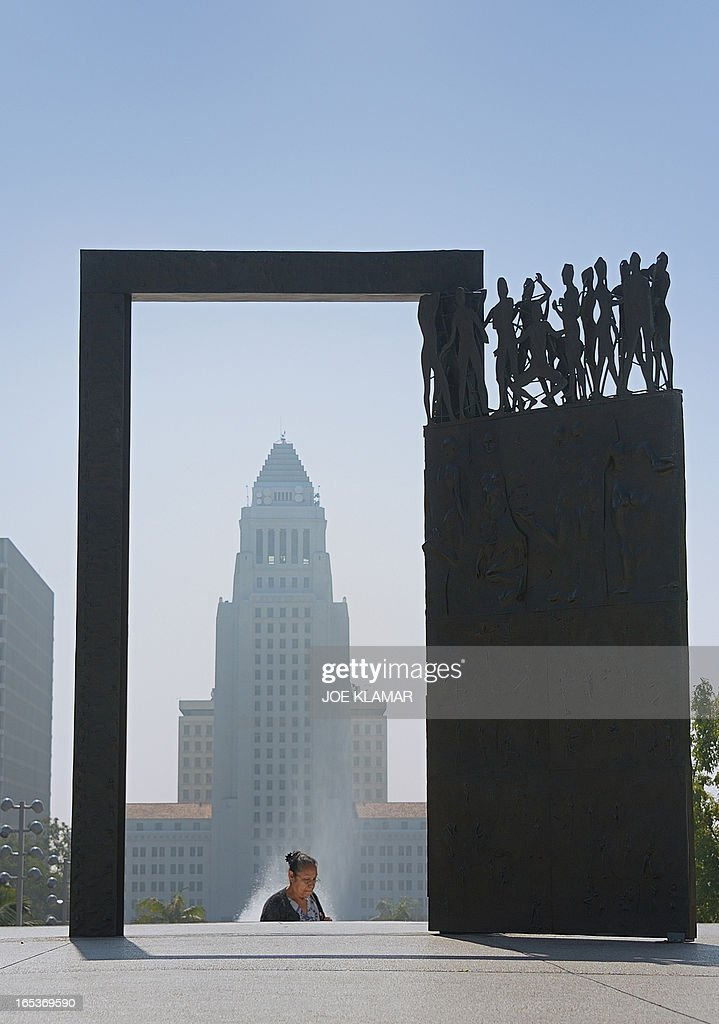 A woman walks by 'Dance Door' in Los Angeles, California on April 03, 2013. 'Dance Door,' by artist Robert Graham, is installed in front of Los Angeles Music Center and it was gift of Frederic R Weisman. The Los Angeles City Hall is in the background.
