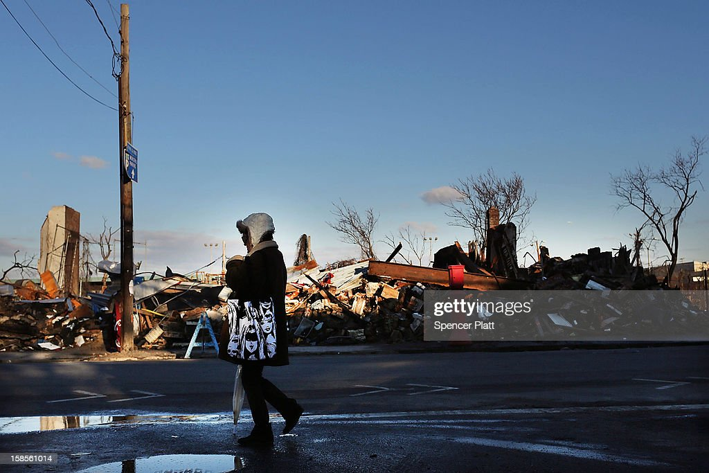 A woman walks by demolished businesses and homes in the heavily damaged Rockaway neighborhood, where a large section of the iconic boardwalk was washed away on November 19, 2012 in the Queens borough of New York City. As the holidays approach after Superstorm Sandy slammed into parts of New York and New Jersey, thousands of residents and businesses are still recovering from the devastation.