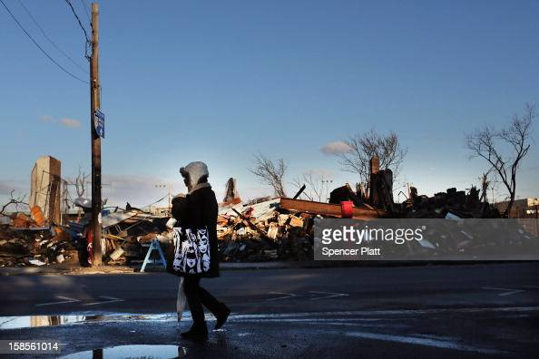 A woman walks by demolished businesses and homes in the heavily damaged Rockaway neighborhood where a large section of the iconic boardwalk was...