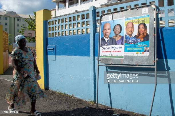 A woman walks by electoral posters in front of a polling station during the secound round of the French legislative elections in PointeaPitre on June...