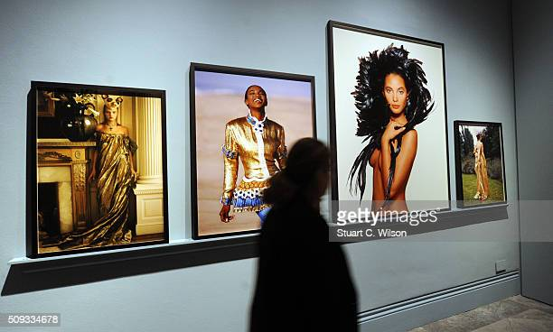 A woman walks by framed photos at the press preview for 'Vogue 100 A Century of Style' exhibiting the photographs that has been commissioned by...