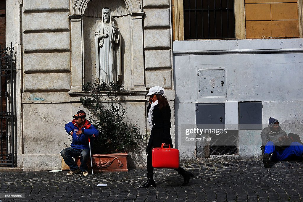 A woman walks by homeless men panhandling in front of of a Catholic church on March 15, 2013 in Rome, Italy. Newly elected Pope Francis, formerly Cardinal Jorge Mario Bergoglio of Buenos Aires, has been a strong advocate for the poor and disenfranchised throughout the world. A Jesuit, Francis has followed the tradition of his order whose members live spartan, communal lives of poverty. Many analysts believe his papacy will see increased outreach and advocacy for the poor.