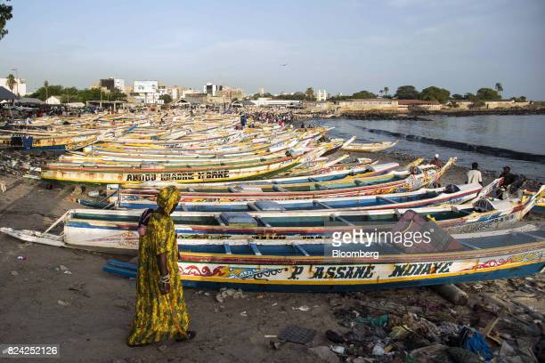 A woman walks by hundreds of painted fishing boats at the Soumbedioune fish market in Dakar Senegal on Friday July 28 2017 Senegalese voters will...