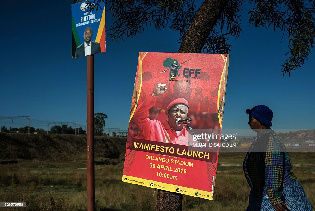 A woman walks by local elections campaign posters ahead of South African opposition radical party Economic Freedom Fighters manifesto launch at Soweto's Orlando Stadium on April, 30, 2016 in Johannesburg. Around 40,000 people turned Orlando stadium in Soweto into a sea of red as supporters roared their approval of fiery EFF leader Julius Malema's promises to seize white-owned land without compensation and nationalise the banks, targeting white privilege and the ruling African National Congress. / AFP / MUJAHID