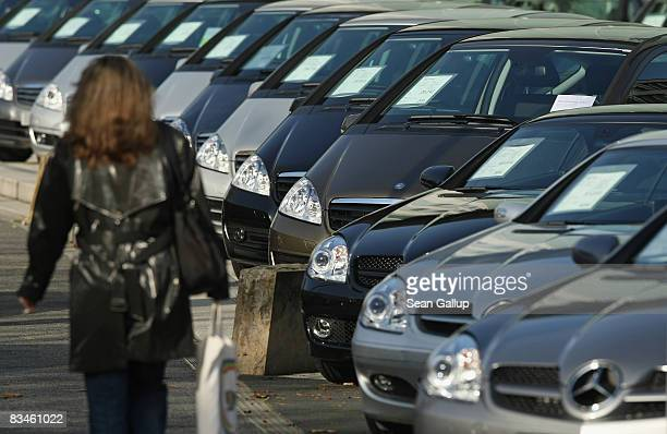 A woman walks by MercedesBenz cars standing at a car dealership on October 28 2008 in Berlin Germany Daimler which owns MercedesBenz has said it will...