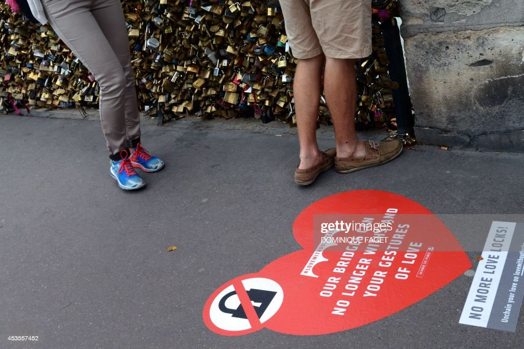 A woman walks by stickers urging tourists to stop setting padlocks on the railings of the pont de l'archeveche, on August 13, 2014 in Paris. Started by tourists in Paris in 2008, the love locks ritual, which also spread in the early 2000s to cities including New York, Seoul and London, has resulted in the transformation of several bridges : every inch of their railings is now covered with clunky brass padlocks.