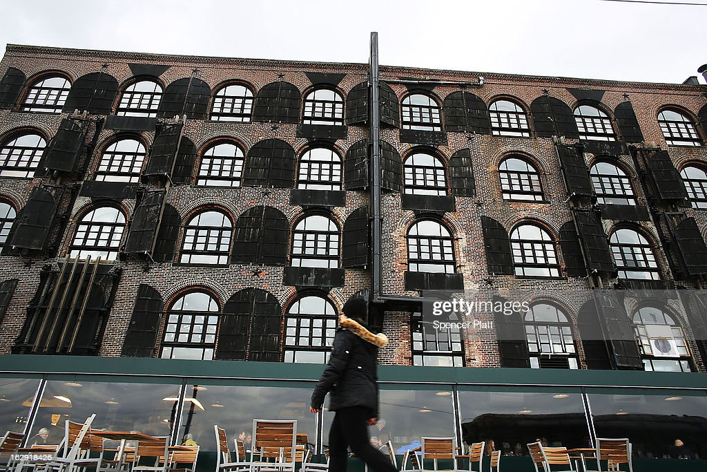 A woman walks by the building housing the newly re-opened Fairway Market on the waterfront in Red Hook on March 1, 2013 in Brooklyn borough of New York City. Fairway, which quickly became a popular shopping destination an an anchor in the struggling community of Red Hook, was closed following severe flooding during Hurricane Sandy on October 29, 2012. Like the rest of Red Hook, Fairway has struggled to quickly re-open in a neighborhood that lost dozens of businesses during the storm. The re-opening, which included a ceremony and ribbon cutting featuring Miss America and Mayor Michael Bloomberg, is being trumpeted as the Red Hook neighborhood's official comeback since the storm.