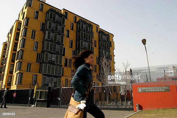 A woman walks by the diplomatic apartments inside the compound of the German school after several suspected asylum seekers were transfered there...