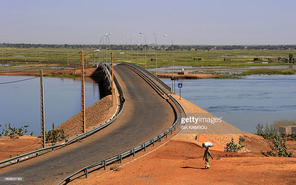 A woman walks by the Gao bridge on the Niger river guarded by French soldiers on February 3, 2013 in Gao. France said it carried out major air strikes today near Kidal, the last bastion of armed extremists chased from Mali's desert north in a lightning French-led offensive.