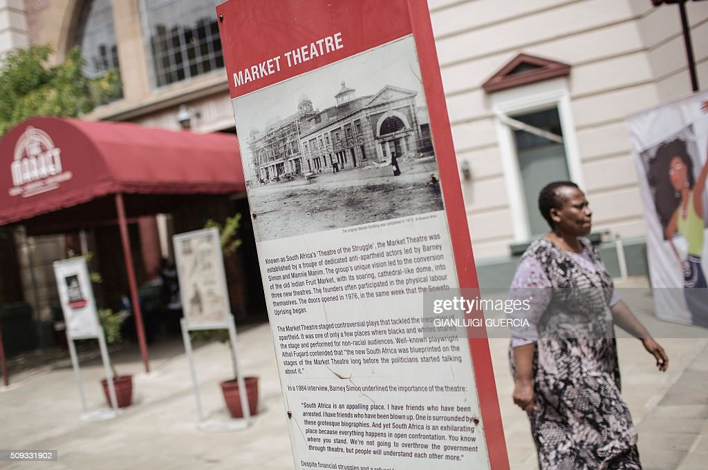 A woman walks by the main entrance of the Historic Market Theatre in Johannesburg on February 10, 2016. In 2016 the iconic Market Theatre marks its 40th anniversary, and as part of the celebrations some of its most socially relevant production will be revived to entertain and challenge a new audience. The Market Theatre was founded by theatre thespians Mannie Manim and Simon Barney, who were disturbed by the absence of a theatre that represented the voice of the majority or reflected what was happening in the skewed society of that era. / AFP / GIANLUIGI GUERCIA