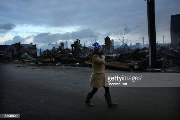 A woman walks by the remains of homes and businesses burned down in the Rockaway neighborhood during Hurricane Sandy on October 31 2012 in the Queens...