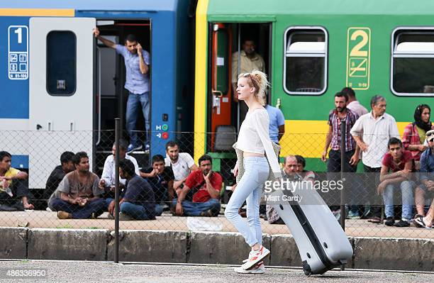 A woman walks by with a suitcase as migrants refuse to be taken to a refugee camp from a train that has been held at Bicske station on September 3...