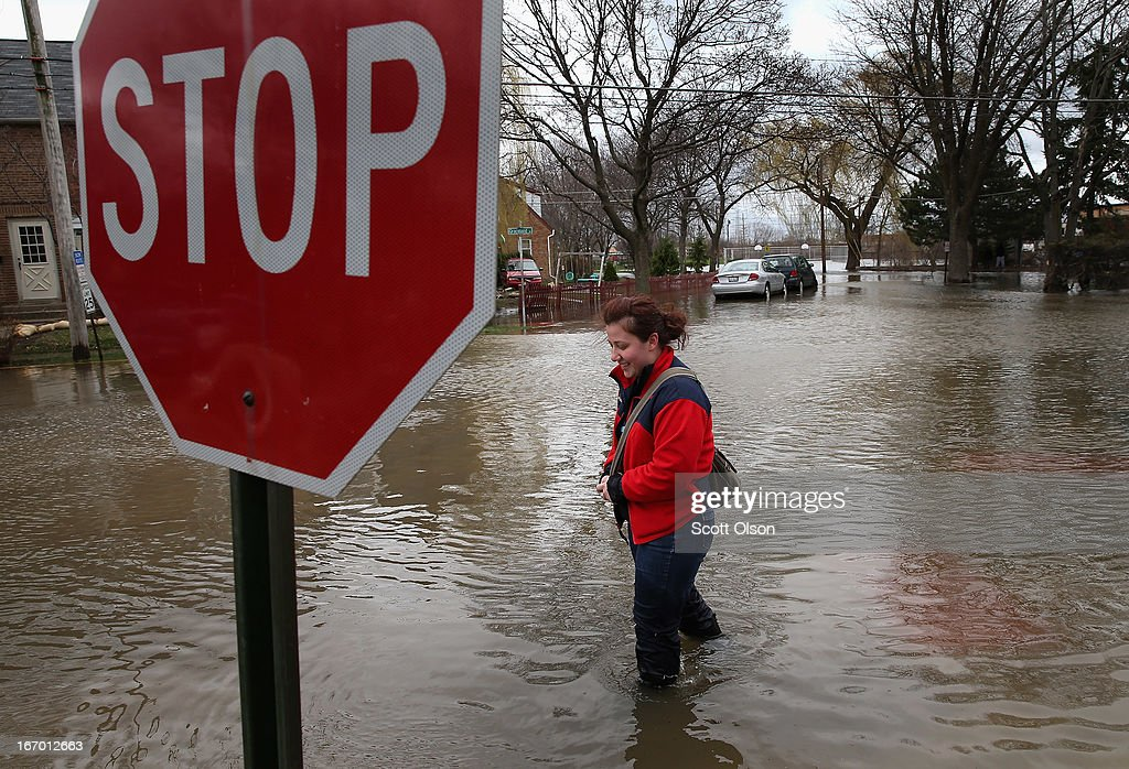 A woman walks down a flooded sidewalk on April 19, 2013 in Des Plaines, Illinois. The suburban Chicago town is battling floodwater from the Des Plaines River which is expected to crest at a record 11 feet later today. Record-setting rains and rising rivers have caused wide-spread flooding in many Illinois communities.
