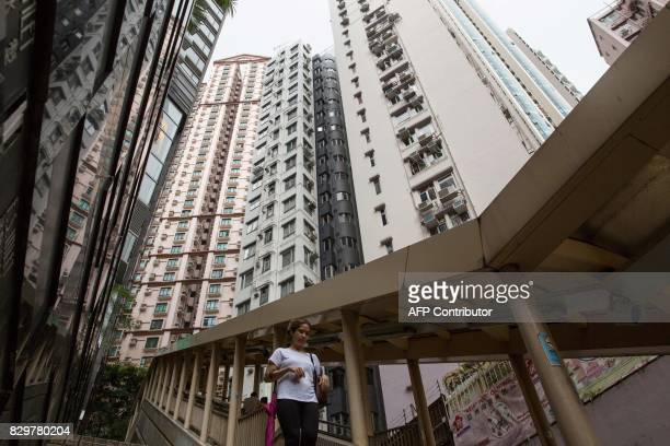 A woman walks down a path as highrise residential buildings installed with air conditioning units are seen in the background in Hong Kong's MidLevels...