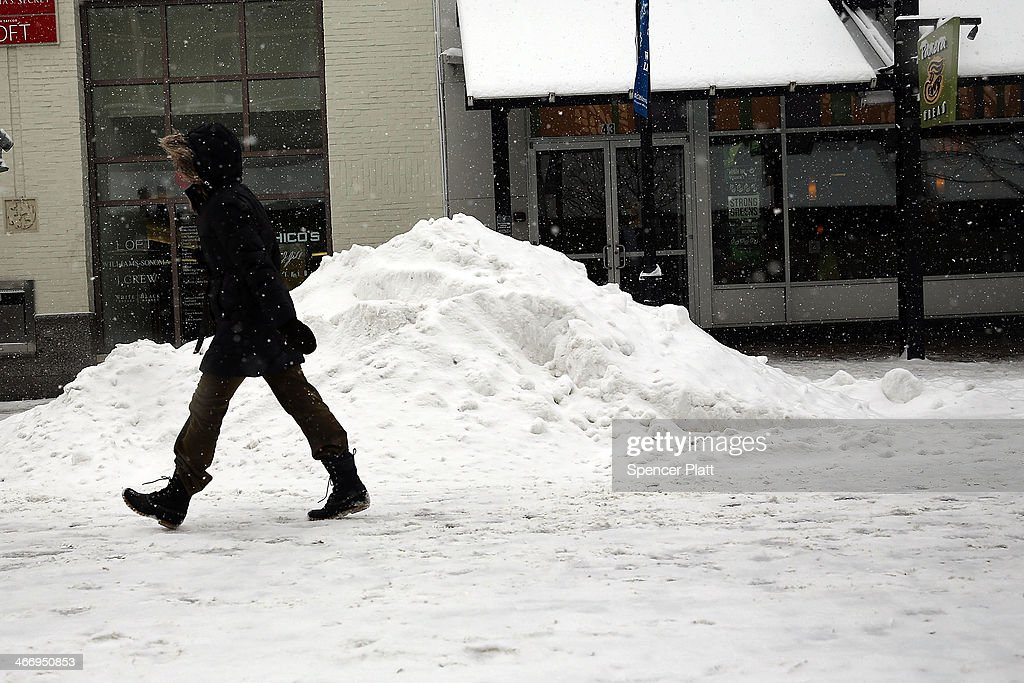 A woman walks down a street during heavy snow on February 5, 2014 in Burlington, Vermont. Burlington, and much of the Northeast, received another mix of wintery weather on Wednesday causing traffic accidents and hundreds of flight cancelations.