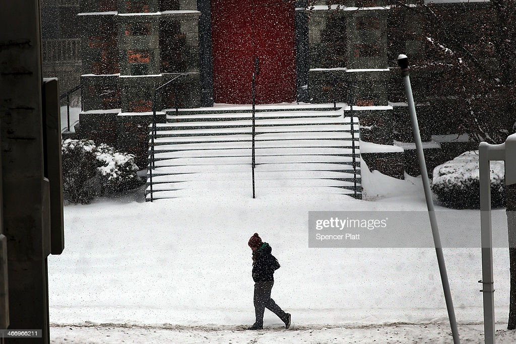 A woman walks down a street during heavy snow on February 5, 2014 in Burlington, United States. Burlington, and much of the Northeast, received another mix of wintery weather on Wednesday causing traffic accidents and hundreds of flight cancelations.