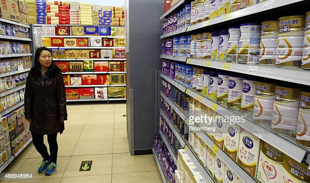 A woman walks down an aisle selling baby formula at a supermarket in Beijing China on Saturday March 14 2015 China is the world's largest dairy...