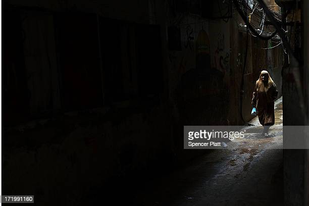 A woman walks down an alley in a poor neighborhood with a high concentration of Syrian refugees on June 30 2013 in Beirut Lebanon Currently the...
