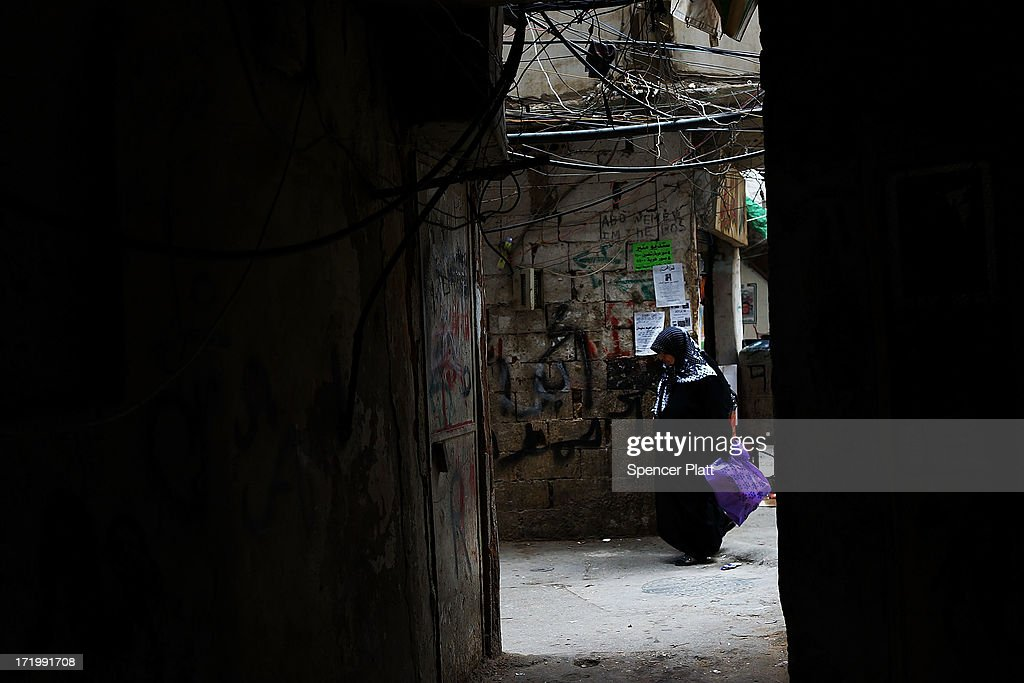 A woman walks down an alley in a poor neighborhood with a high concentration of Syrian refugees on June 30, 2013 in Beirut, Lebanon. Currently the Lebanese government officially hosts 546,000 Syrians with an estimated additional 500,000 who have not registered with the United Nations. Lebanon, a country of only 4 million people, is now home to the largest number of Syrian refugees who have fled the conflict. The situation is beginning to put a huge social and political strains on Lebanon as there is currently no end in sight to the war in Syria.