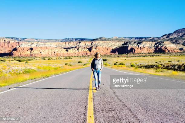 Frau geht auf Mitte des schönen leeren Western Highway