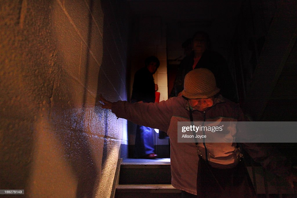 A woman walks down the dark stairwell at the Meltzer Towers Housing Project giving out food and water to elderly and disabled residents November 2, 2012 in New York City. The electricity, heat and water are out in all New York public housing buildings. Limited public transit has returned to New York. With the death toll continuing to rise and millions of homes and businesses without power, the U.S. east coast is attempting to recover from the effects of floods, fires and power outages brought on by Superstorm Sandy.