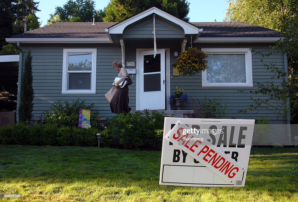 A woman walks down the steps of a home with a sale pending sign in its front yard in Eugene Oregon Wednesday Aug 1 2007 Americans unexpectedly signed...