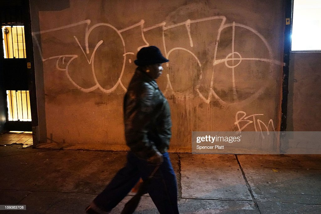 A woman walks down the street near where a rally and vigil was held at the location where a 16-year-old boy was shot last Tuesday evening, on January 12, 2013 in the Crown Heights neighborhood of the Brooklyn borough of New York City. The gathering was sponsored by the local group S.O.S., which is a community-based effort to end gun violence. S.O.S. holds the gatherings at all shooting locations in Crown Heights to draw attention to the violence and to encourage a community response to the shootings. While murders were down for 2012 in New York City, gun violence continues to plague many communities.