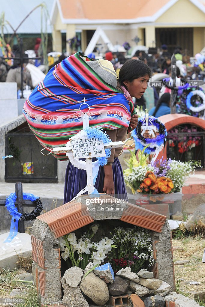 A woman walks during the traditional celebration Feast of all Saints where families reunite in the cementery with the belief that the soul will visit the deceased relatives. They wait for them with a table full of flowers and tantawas (colorful bread with a mask) and drinks on November 02, 2012 in La Paz, Bolivia.