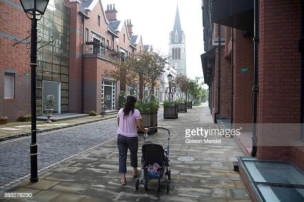 A woman walks her baby through the empty streets of Thames Town an imitation English village in China The architecture here imitates classic English...