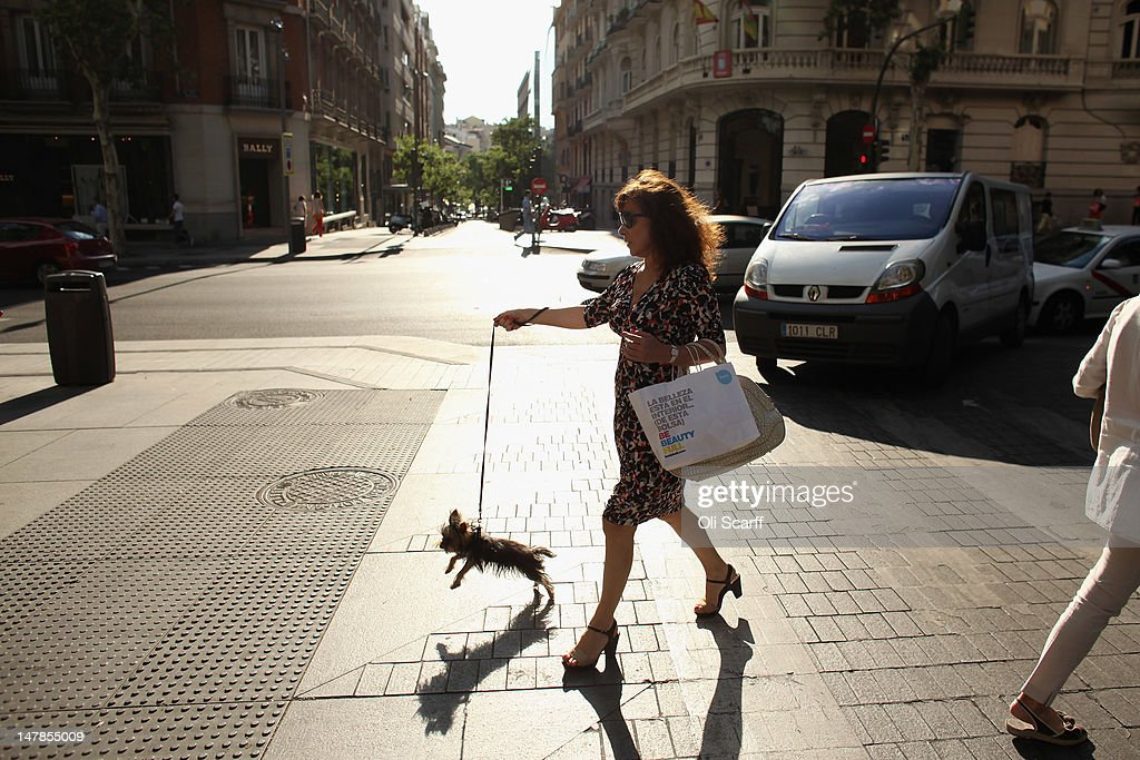 A woman walks her dog along the affluent shopping street of Calle de Serrano on July 4, 2012 in Madrid, Spain. Despite having the fourth largest economy in the Eurozone, the economic situation in Spain remains troubled with their unemployment rate the highest of any Eurozone country. Spain is currently administering billions of euros of spending cuts and tax increases in a bid to manage its national debt. Spain also has access to loans of up to 100 billion euros from the European Financial Stability Facility which will be used to rescue the country's banks that have been badly affected by a crash in property prices.