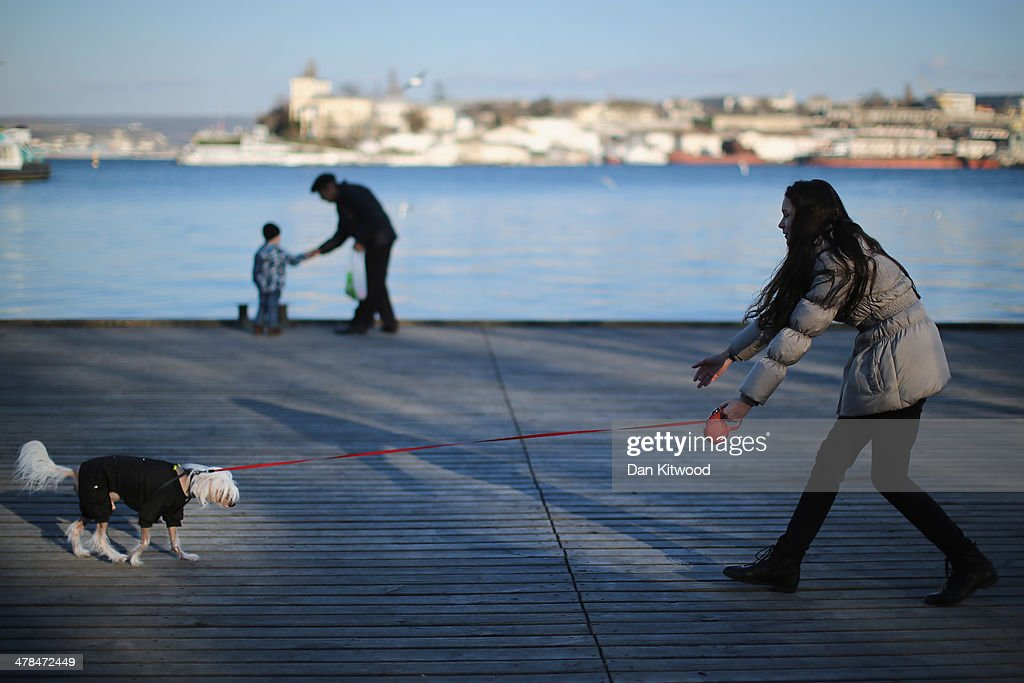 A woman walks her dog along the sea front on March 13, 2014 in Sevastopol, Ukraine. As the standoff between the Russian military and Ukrainian forces continues in Ukraine's Crimean peninsula, world leaders are pushing for a diplomatic solution to the escalating situation. Crimean citizens will vote in a referendum on 16 March on whether to become part of the Russian federation.